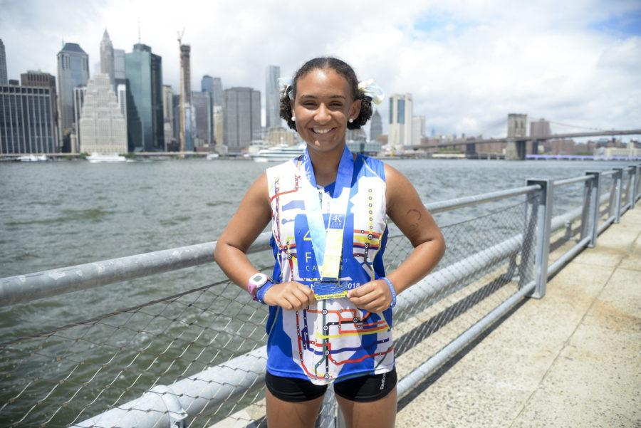 """Monica Henderson poses with her medal that reads """"4k for cancer finisher"""" after finishing her 4,000-mile run on Pier 2 in Brooklyn. (Photo by Anna Bongardino   Visual Editor)"""