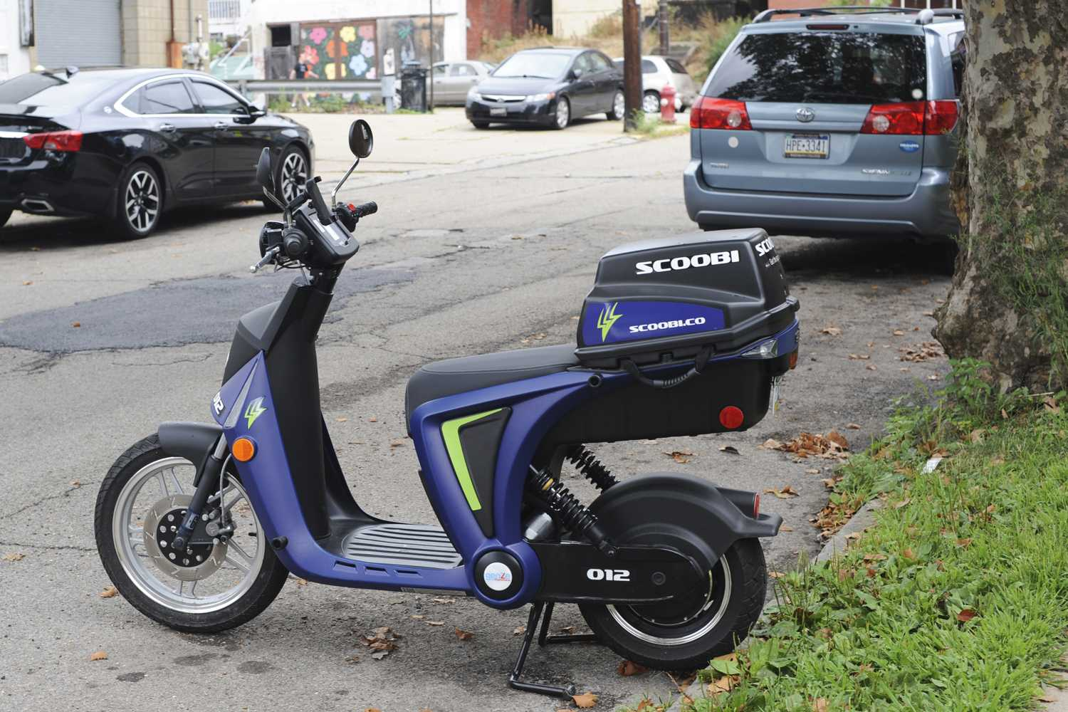 One of 100 Scoobi electric scooters placed around Pittsburgh July 21 sits on Penn and Roup avenues in Friendship. Anyone 18 and older with a valid driver's license can rent the electric scooters using a smartphone. (Photo by Anne Amundson | Staff Photographer)