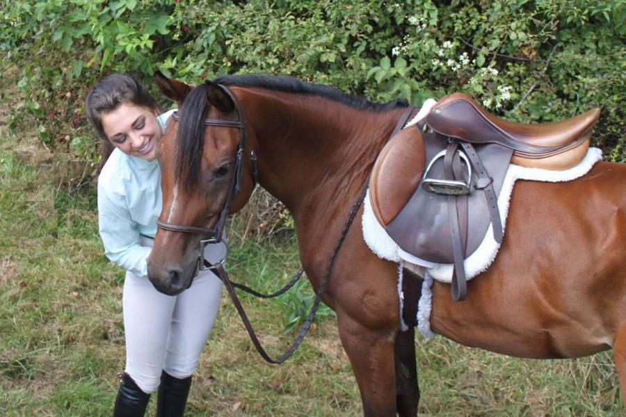 Micah Lisi, Pitt Equestrian club president and a senior biology and chemistry double major, stands with her horse Sienna.