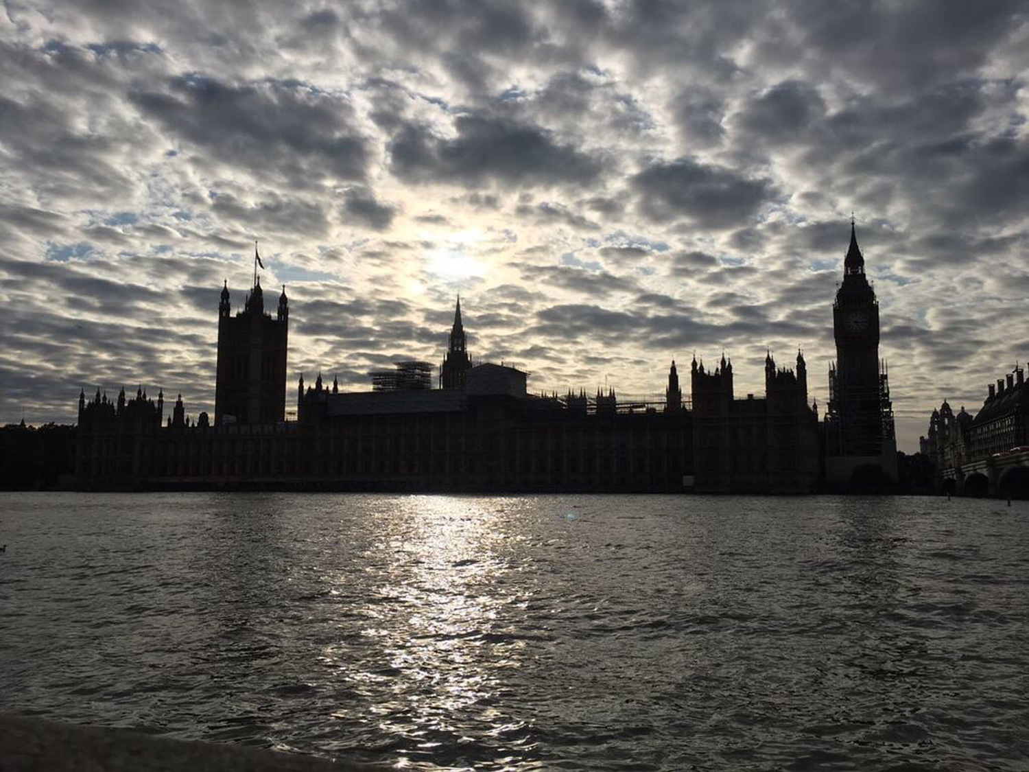 The London skyline appears backlit on a cloudy day.