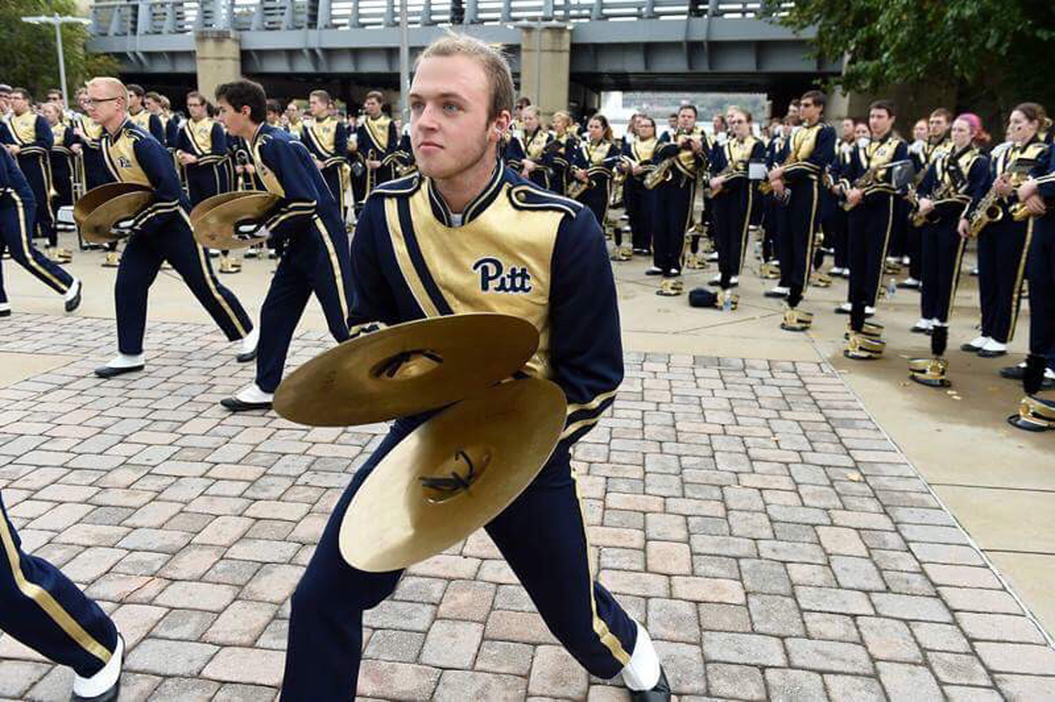 Senior music composition and economics major Jonathan Heller performs with the percussion section of Pitt Band outside Heinz Field.
