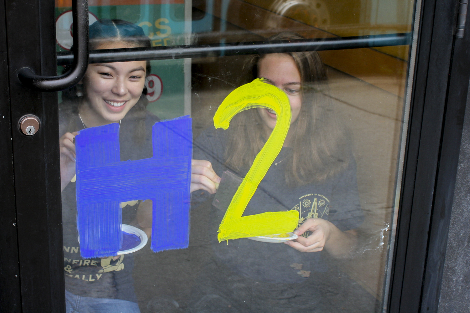 "First-years Lily McIntire (left) and Alden Paine paint ""H2P"" on Popeye's door Monday for Paint the Town — an event hosted by Pitt Student Alumni Association — in preparation for Homecoming."
