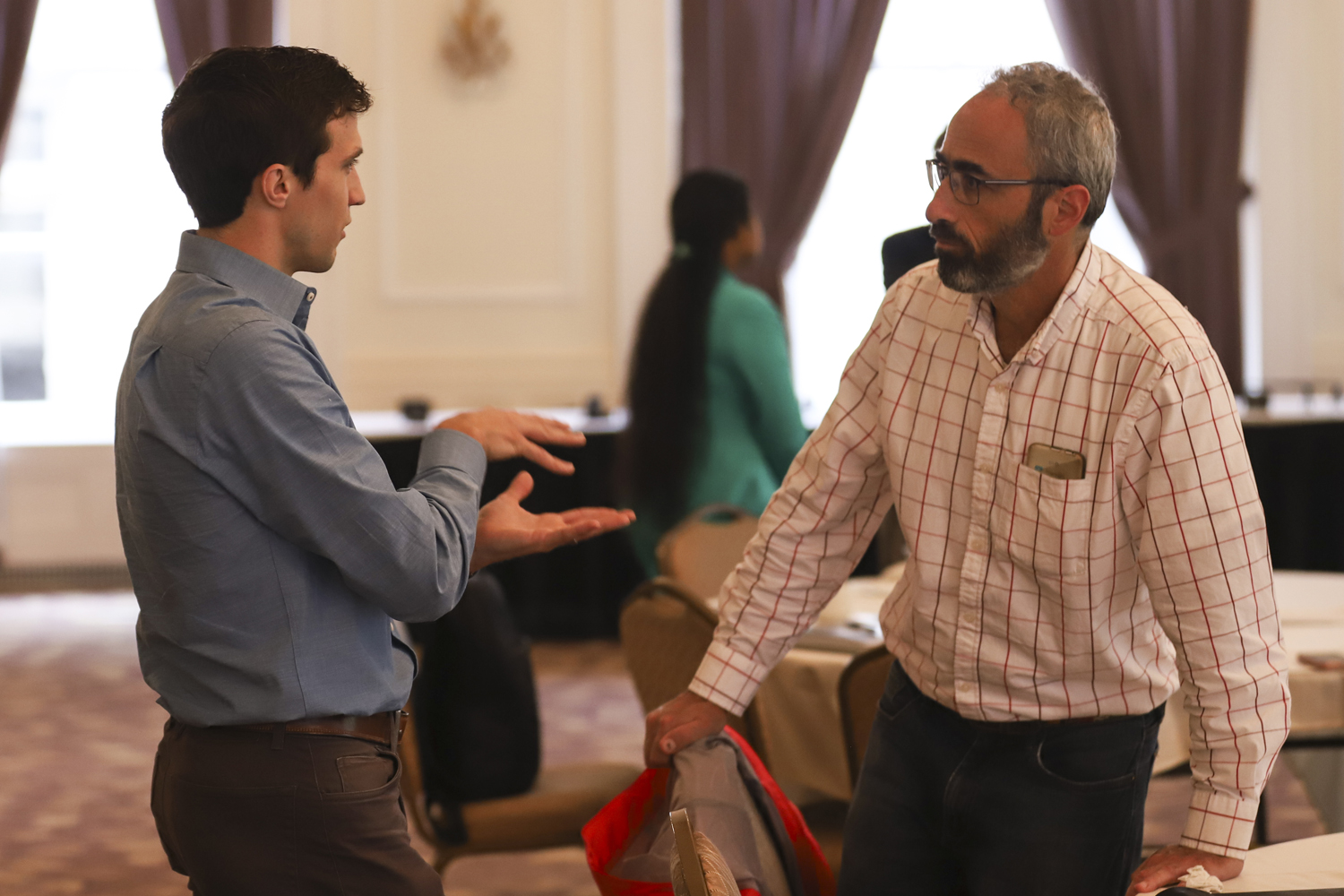 "Graduate electrical engineering student John Kieffer (left) speaks with Daniel Mosse — a computer science professor at Pitt — after the Empowering Communities through Energy Efficiency event Monday. ""Those two words get my endorphins flowing,"" Mosse said of the event's title."