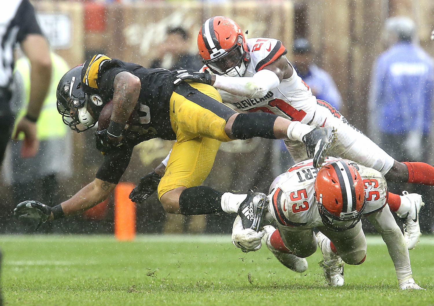 Cleveland Browns Denzel Ward (top) and Joe Schobert take down Pittsburgh Steelers James Conner during overtime Sunday at FirstEnergy Stadium in Cleveland. The game ended in a 21-21 tie.