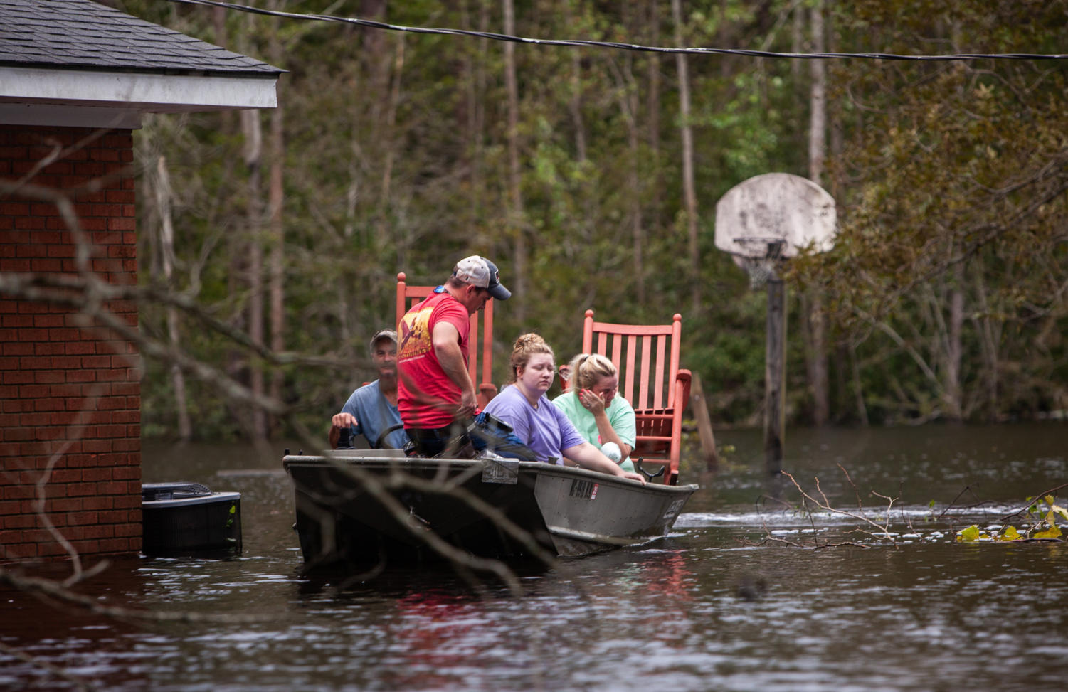 From left, Mike Haddock, 48, Justin Humphrey, 24, Katlyn Humphrey, 19, and Michelle Haddock, 45, remove possessions from the Haddocks' flooded home using a jon boat on Monday, Sept. 17, 2018 in Trenton, N.C. following Hurricane Florence. (Travis Long/Raleigh News & Observer/TNS)