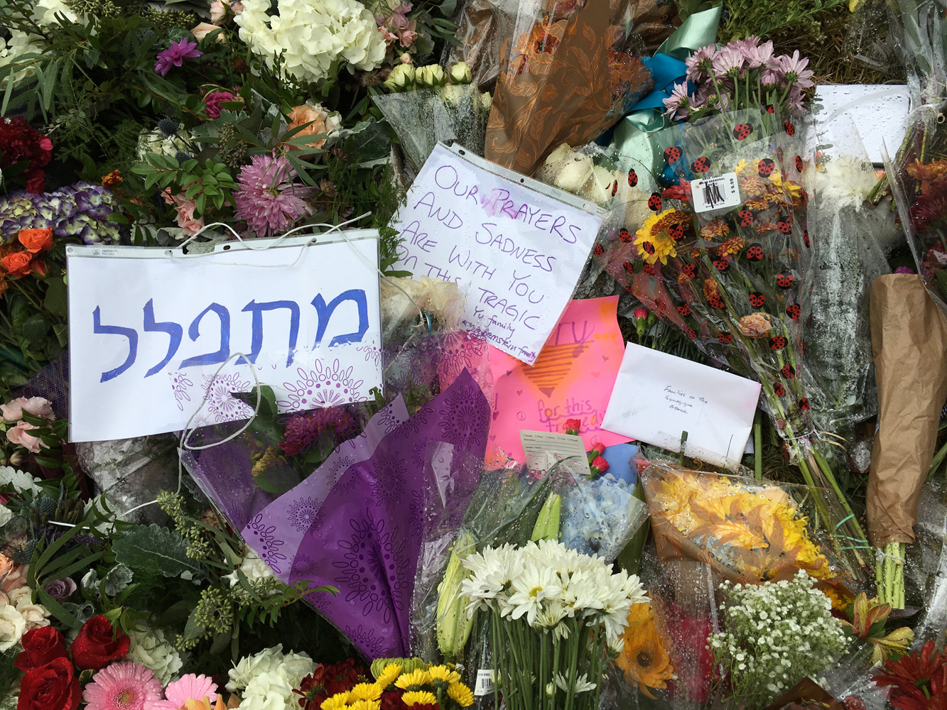 """Pittsburgh community members leave flowers and notes outside the Tree of Life Synagogue, including a sign that says """"praying"""" in Hebrew."""