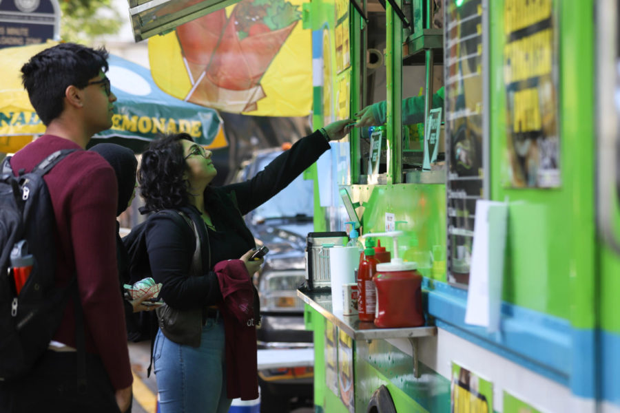 "A student pays for an order at the PGH Halal truck outside the William Pitt Union for Wednesday afternoon's ""International Food Trucks"" event. (Photo by Kaycee Orwig 