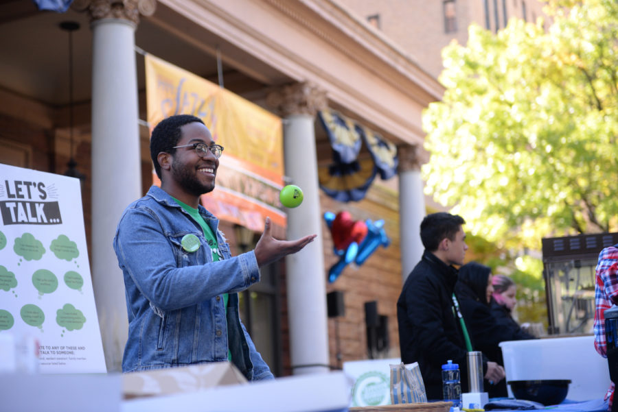 "SGB board member Zechariah Brown hands out ""Let's Talk"" stress balls at SGB's table during Tuesday's ""I Love Pitt Day."""