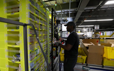 An Amazon worker scans items with a handheld device before putting them in storage pods maneuvered by robots. Amazon announced its plan to roll out a $15-an-hour minimum wage for all of its U.S. employees.