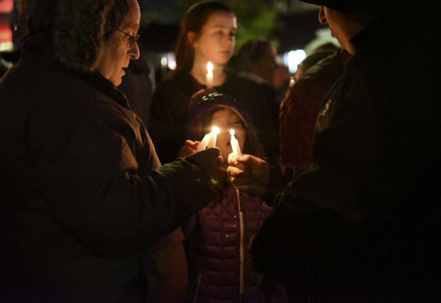 A vigil attendee lights two other attendees' candles during the Saturday night vigil for the Tree of Life Synagogue shooting victims.