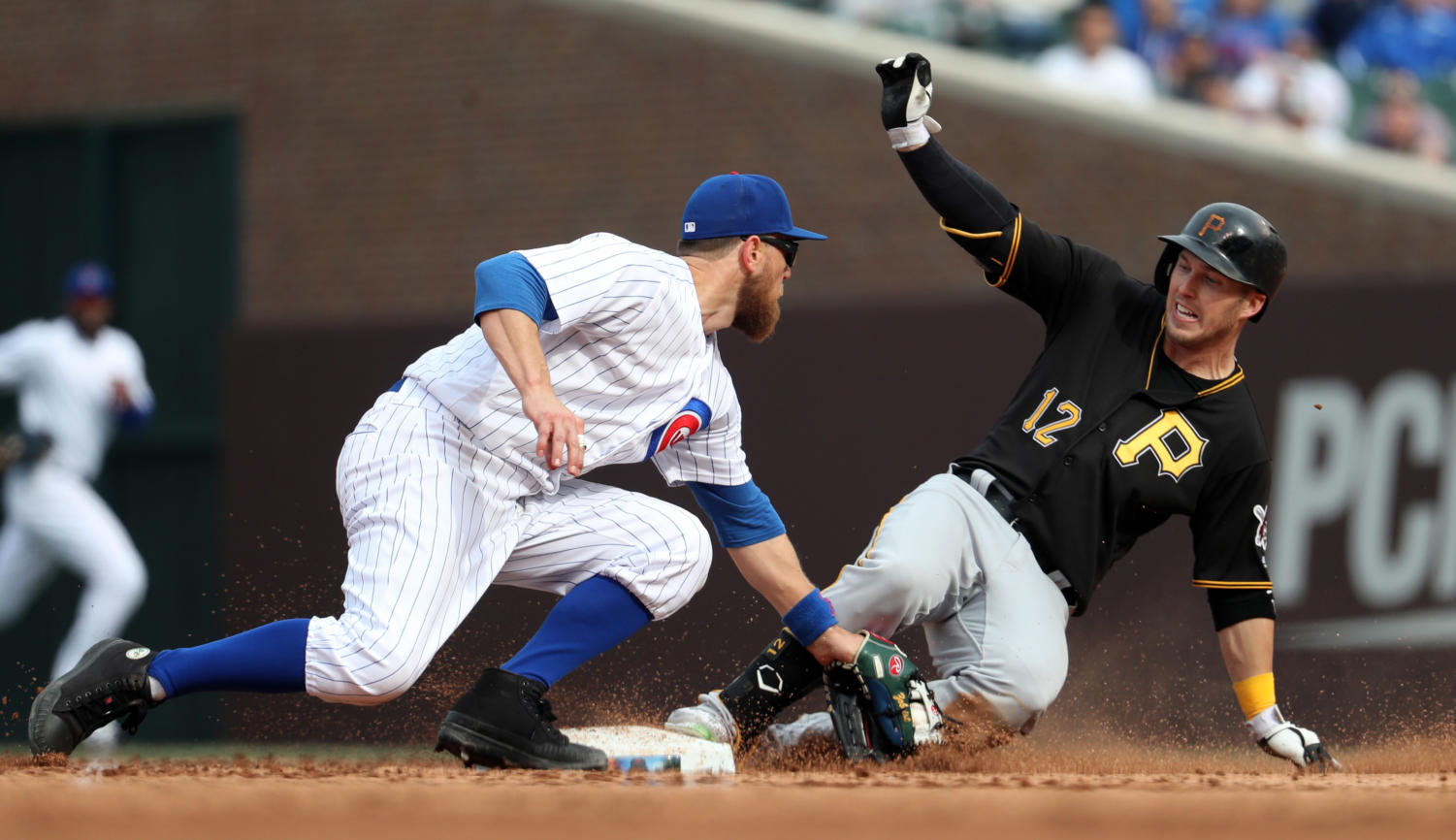 The Pittsburgh Pirates' Corey Dickerson (12) reaches second base with a double ahead of the tag from Chicago Cubs second baseman Ben Zobrist in the ninth inning April 12 at Wrigley Field in Chicago. The Pirates won, 6-1. (Brian Cassella/Chicago Tribune/TNS)