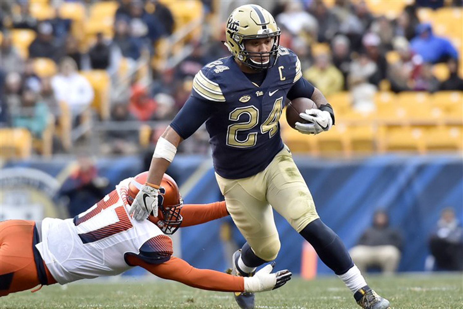 Pitt's James Conner evades Syracuse's Ted Taylor in the second quarter Nov. 26, 2016, at Heinz Field. Pitt won, 76-61.