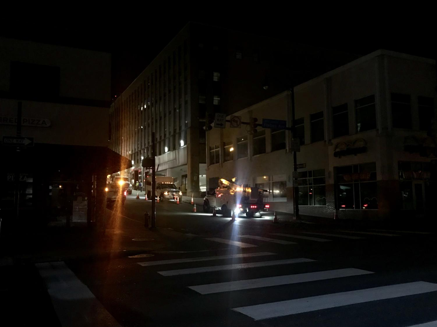 Duquesne Light Company trucks work at the corner of Forbes and Atwood after midnight during a power outage that carried over into early Tuesday morning.
