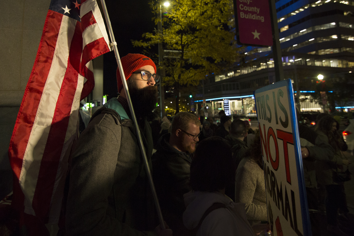 "A protester stands outside City-County Building holding an American flag behind a sign that reads, ""This is not normal."""