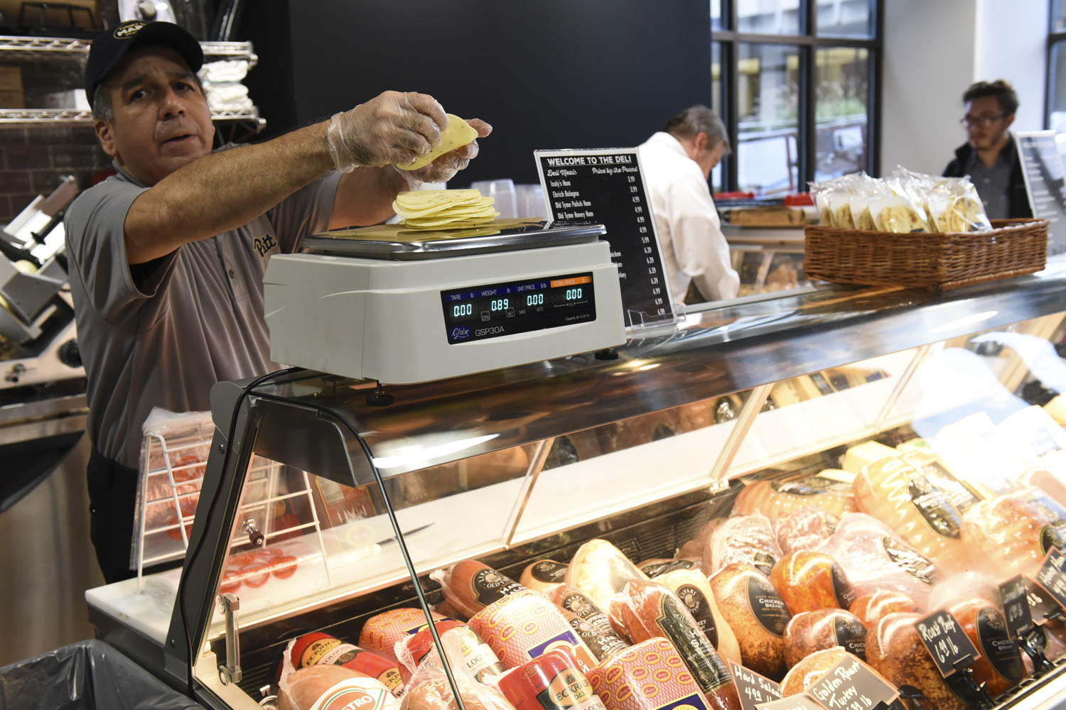 An employee at Forbes St. Market weighs cheese on the deli's scale.
