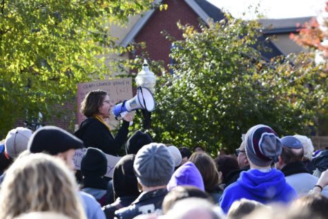 A woman speaks to a crowd of people protesting anti-Semitic violence through a megaphone on Tuesday.