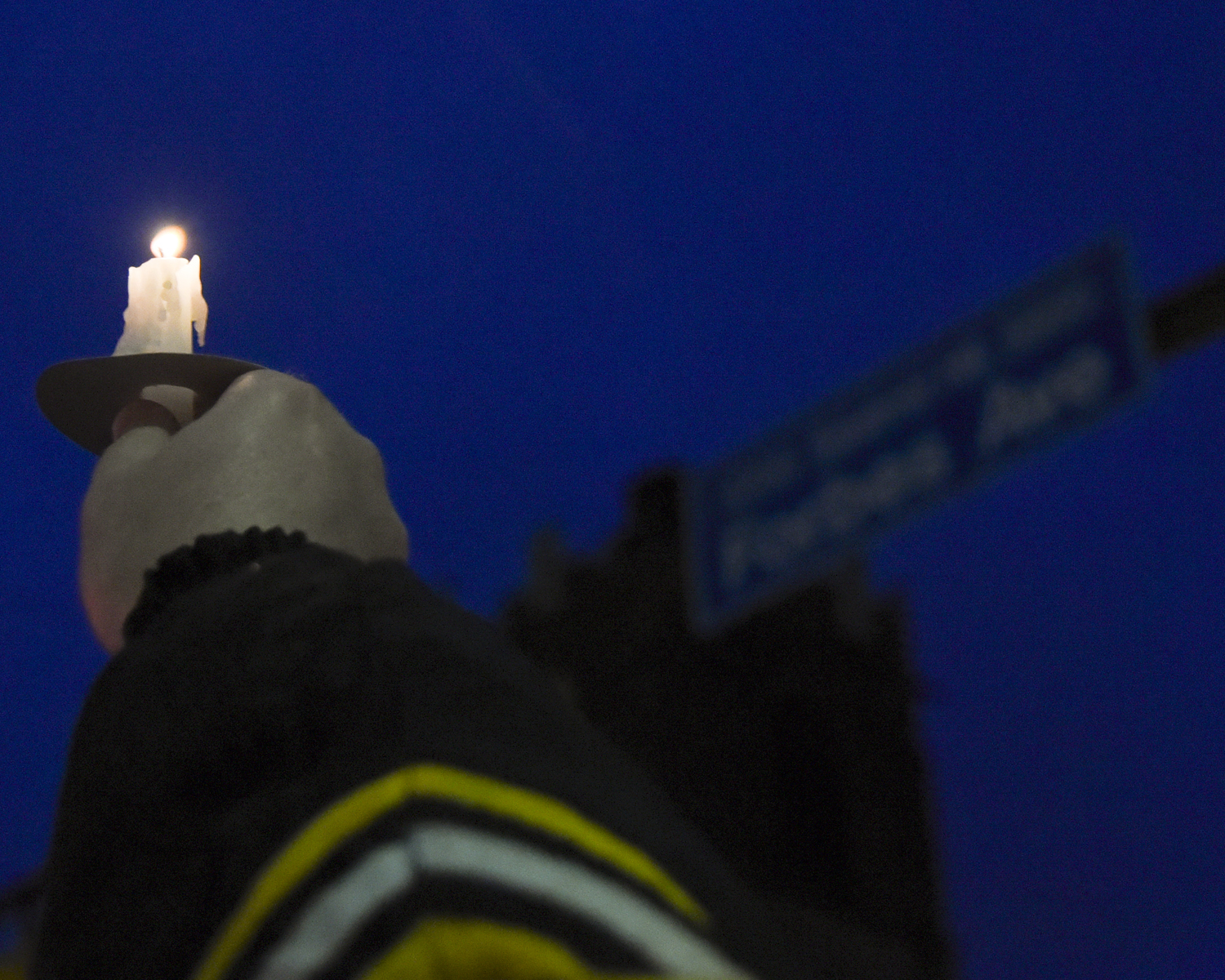 A man holds a candle up to the sky at the Squirrel Hill intersection of Forbes and Murray avenues Saturday evening during a vigil for the victims of the Tree of Life synagogue massacre.