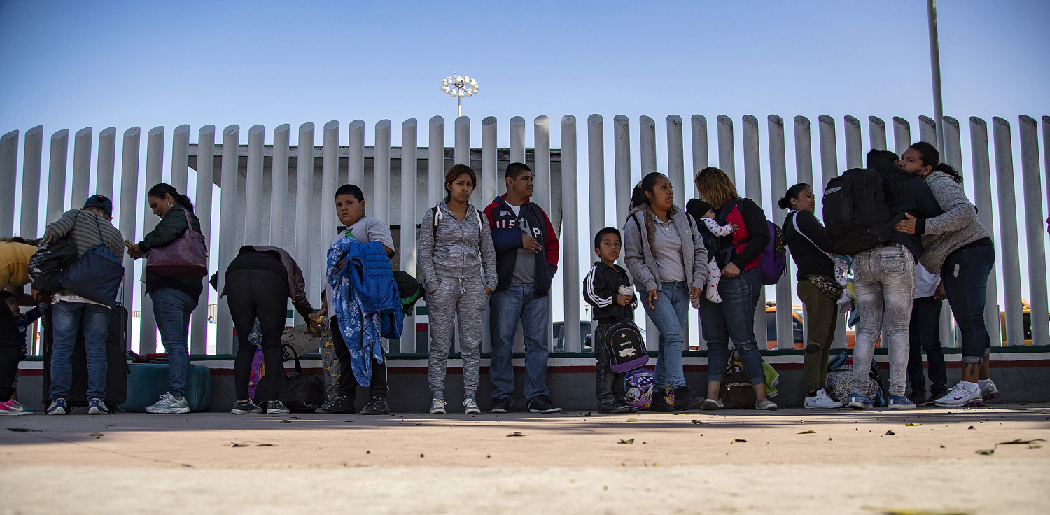Eulalia Dalila Pojoy Cuyuch, 33, of Guatemala (far right) and her family say goodbye to a friend as they wait along the border fence to turn themselves into U.S. Customs on June 14, asking for asylum in Tijuana, Mexico.