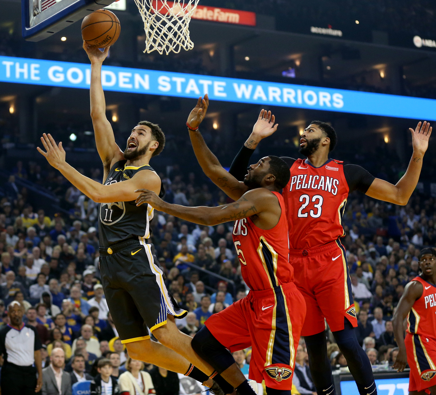 Golden State Warriors' Klay Thompson (11) drives to the hoop against New Orleans Pelicans' E'Twaun Moore (55) and Anthony Davis (23) in the first quarter during their NBA game at Oracle Arena in Oakland, California, on Wednesday, Oct. 31.