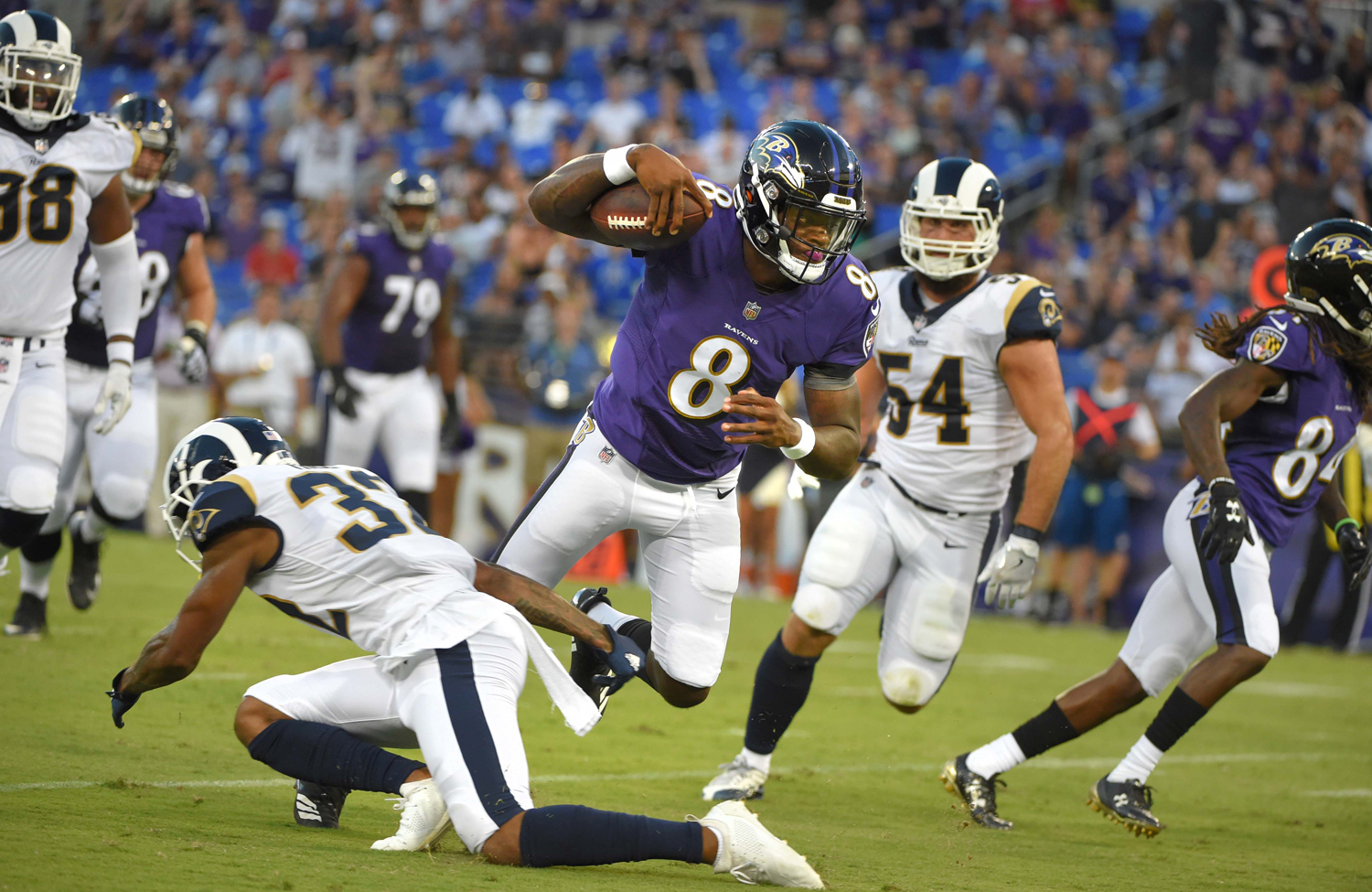 Baltimore Ravens quarterback Lamar Jackson (8) scores a touchdown after making a cut on the Los Angeles Rams' Troy Hill (32) in the first half during a preseason game at M&T Bank Stadium in Baltimore on Aug. 9.