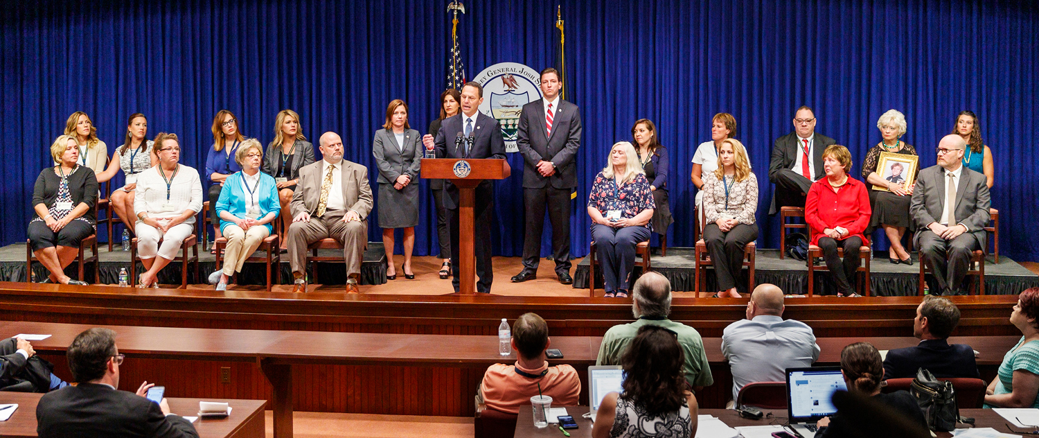 Pennsylvania Attorney General Josh Shapiro, center, speaks on the findings of the grand jury report on child sexual abuse in six Catholic dioceses at the State Capitol, with 16 victims or family members of victims of sexual abuse by Catholic priests seated on stage with him on Aug. 14.
