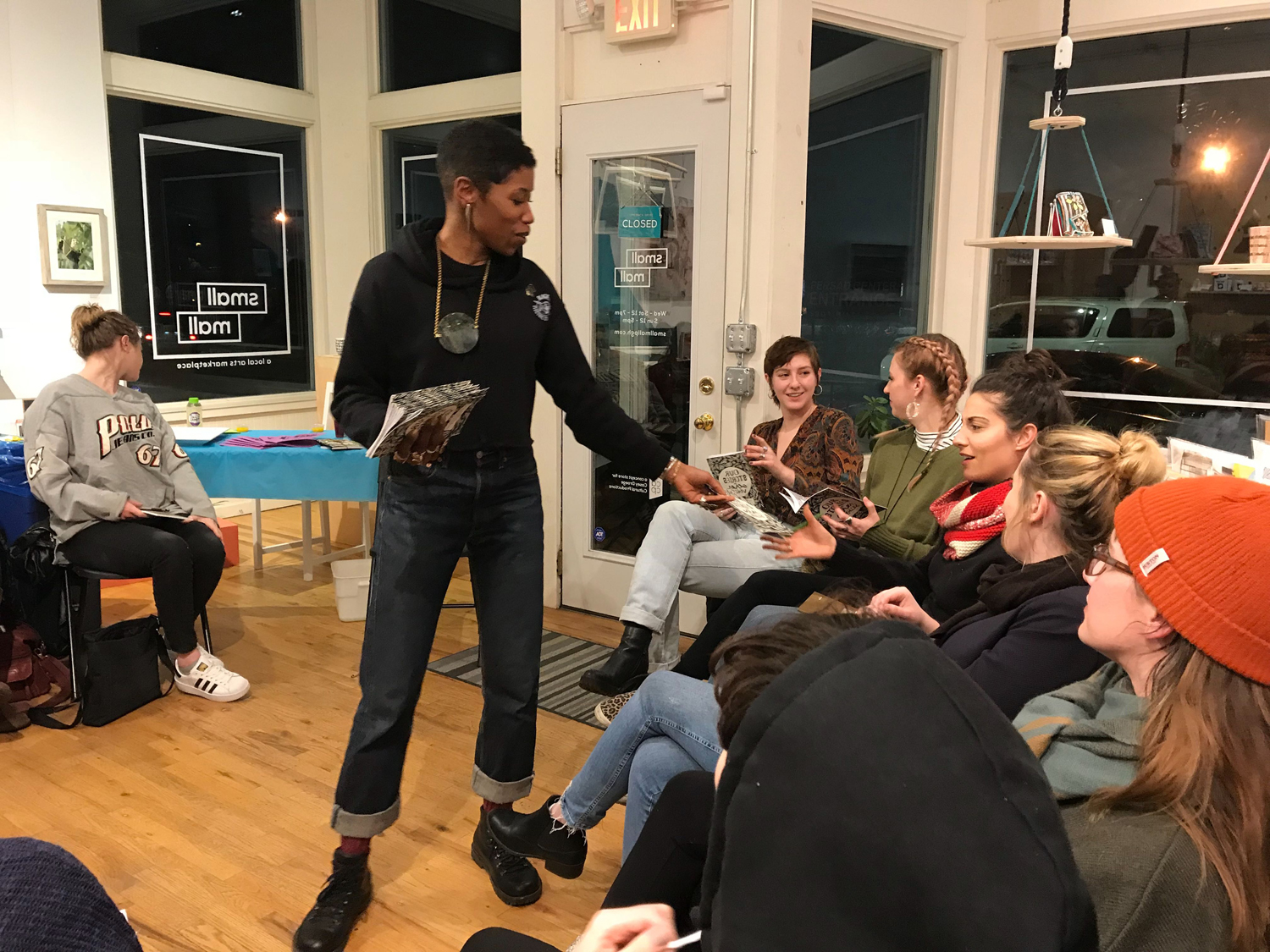 """Atiya Jones distributes copies of """"Our Stories in Other Voices"""" at her Small Mall self-care workshop."""