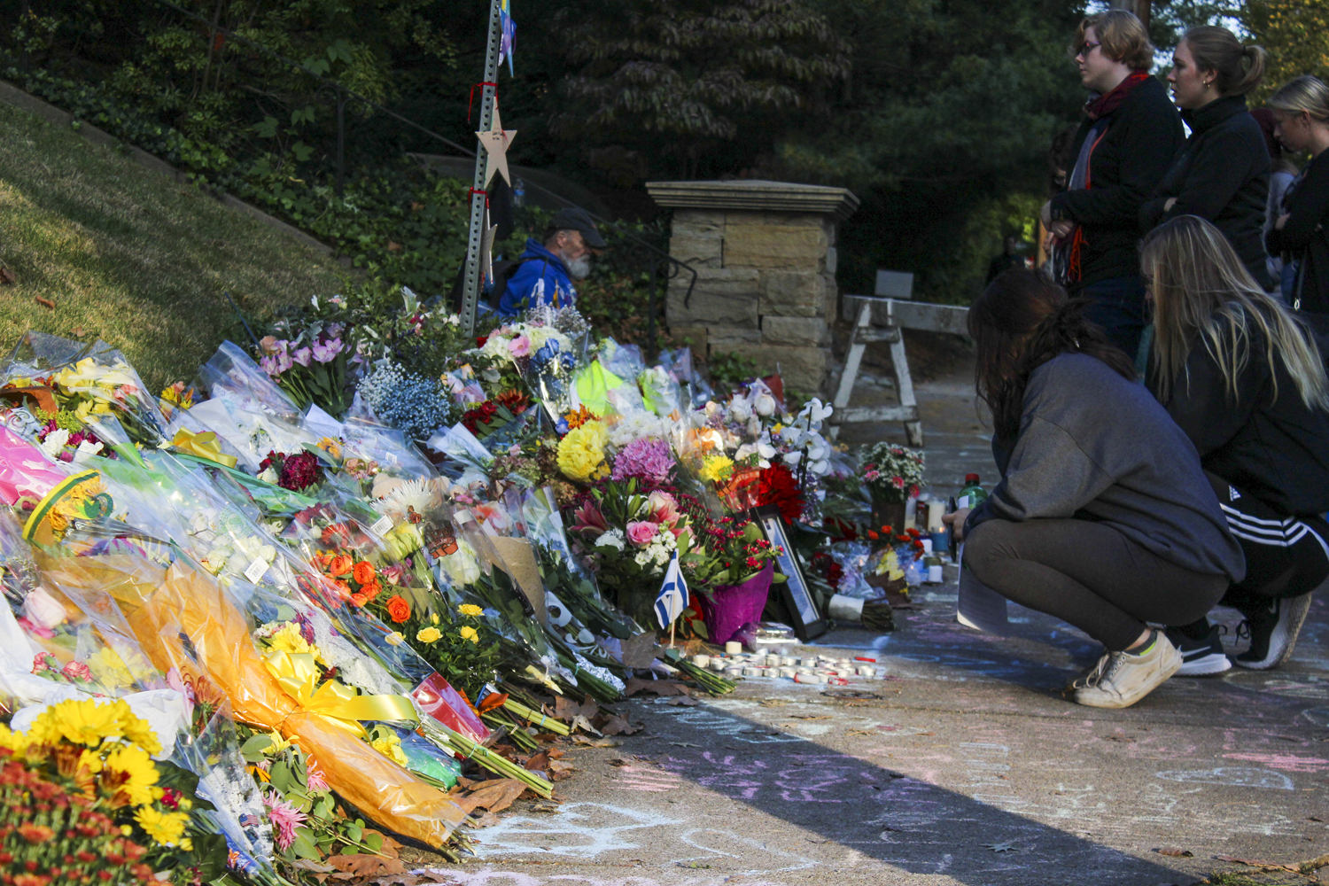 Mourners gather at a small memorial behind police lines near the Tree of Life Synagogue Oct. 30, 2018. On the other side of the barricades, President Donald Trump addressed the nation three days after the deadly Tree of Life shooting.