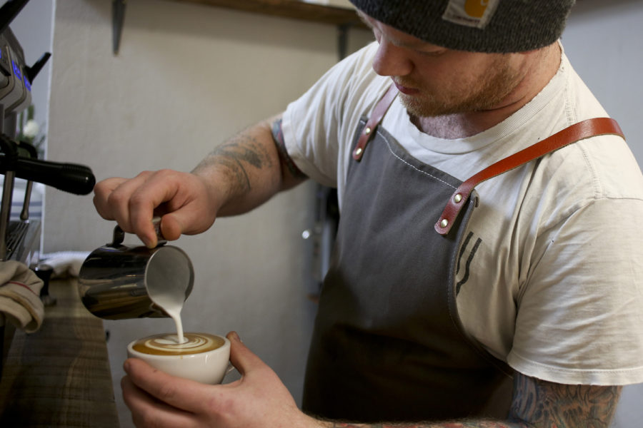 Redhawk Coffee owner Braden Walter pours a latte.
