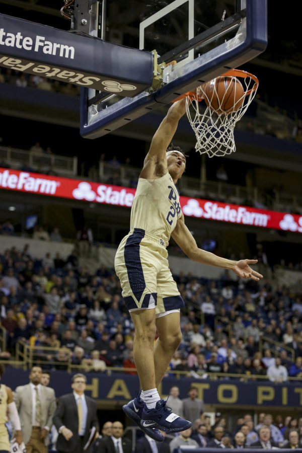 First-year guard Trey McGowens (2) completes a dunk during Pitt's 89-86 victory of Louisville Wednesday evening.