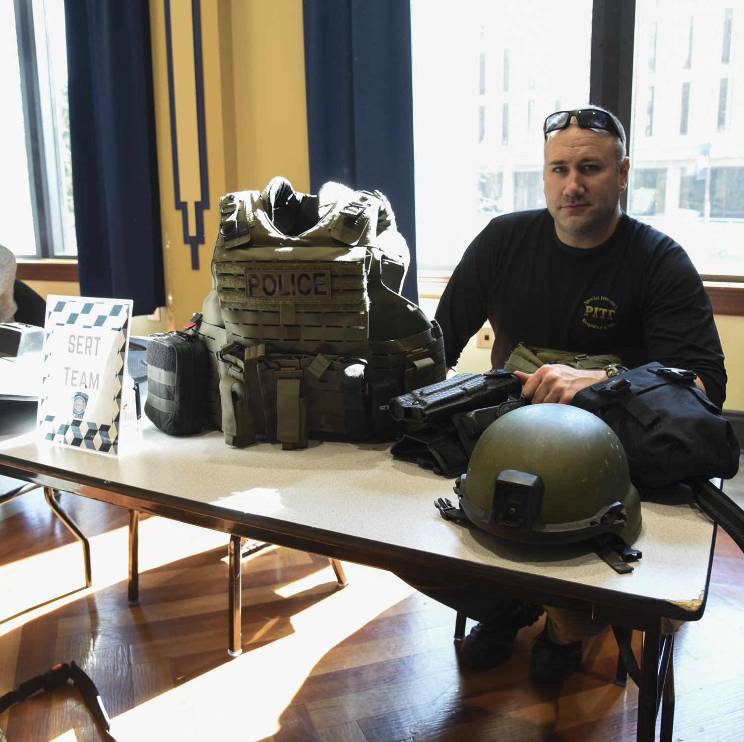 Mike Matta, a detective at the Pitt Police and a member of the Special Emergency Response Team, sits at a table informing visitors about the SERT team.