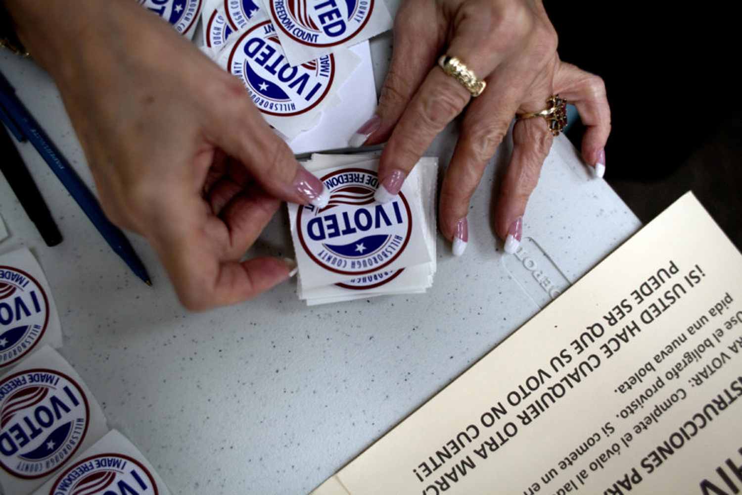 """A poll worker gets """"I Voted"""" stickers ready to hand to voters as they finish up at the ballot booths."""