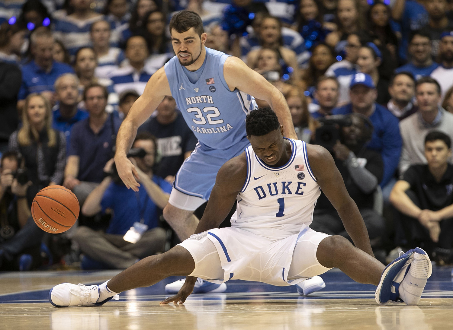 Duke's Zion Williamson (1) falls to the court under North Carolina's Luke Maye (32), injuring himself and damaging his shoe during the first half of the game on Wednesday, Feb. 20 at Cameron Indoor Stadium in Durham, N.C.