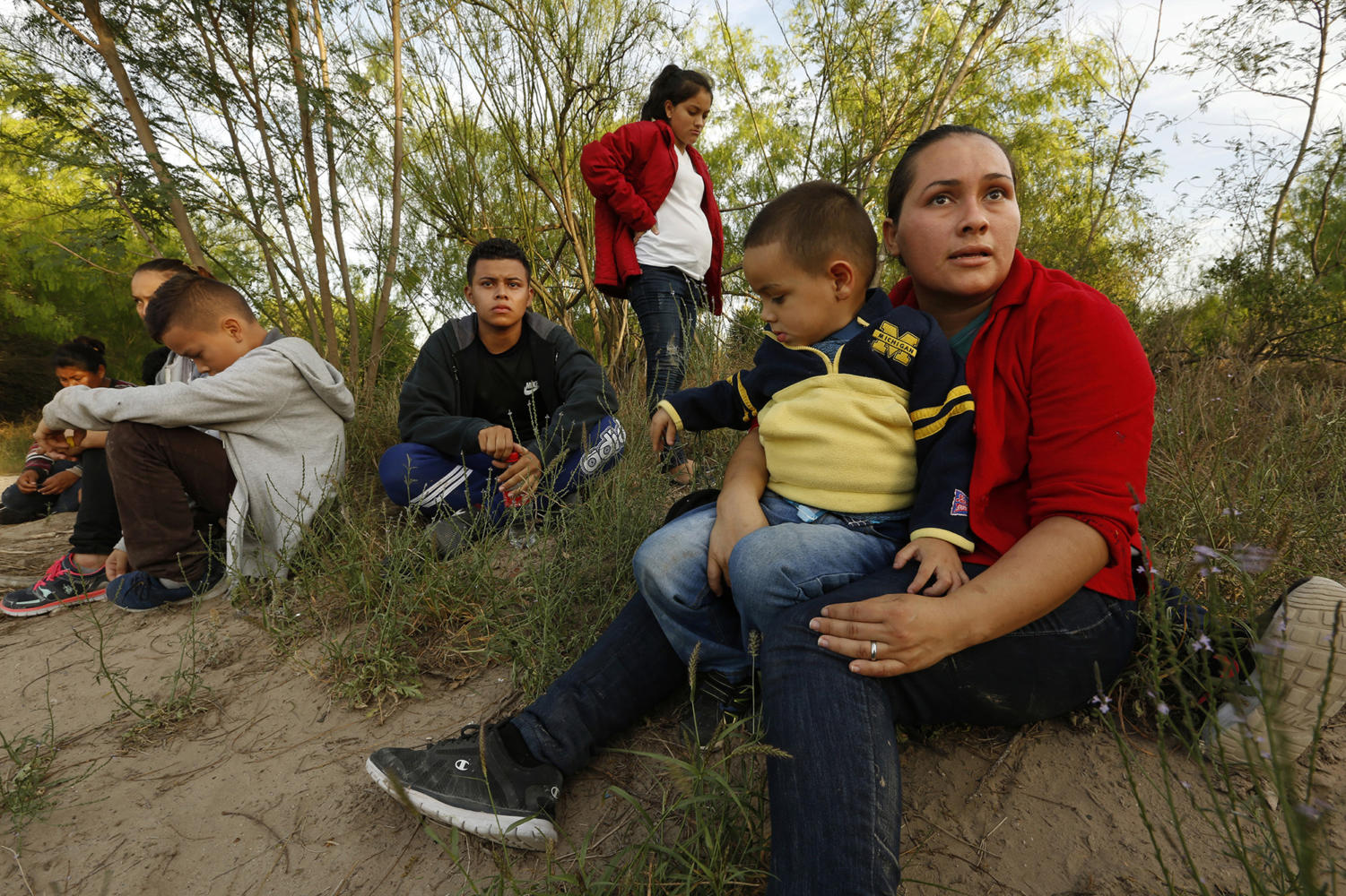 Hayti Alvarado, 26, holds her son Esteban Alvarado, 3, along with her daughter Gabriella Alvarado, 11, (not shown) after being detained near the Rio Grande River. The Alvarado family had to flee their country after Gabriella was threatened at school. A report suggests thousands more children were separated from their families by the Trump administration than previously disclosed.