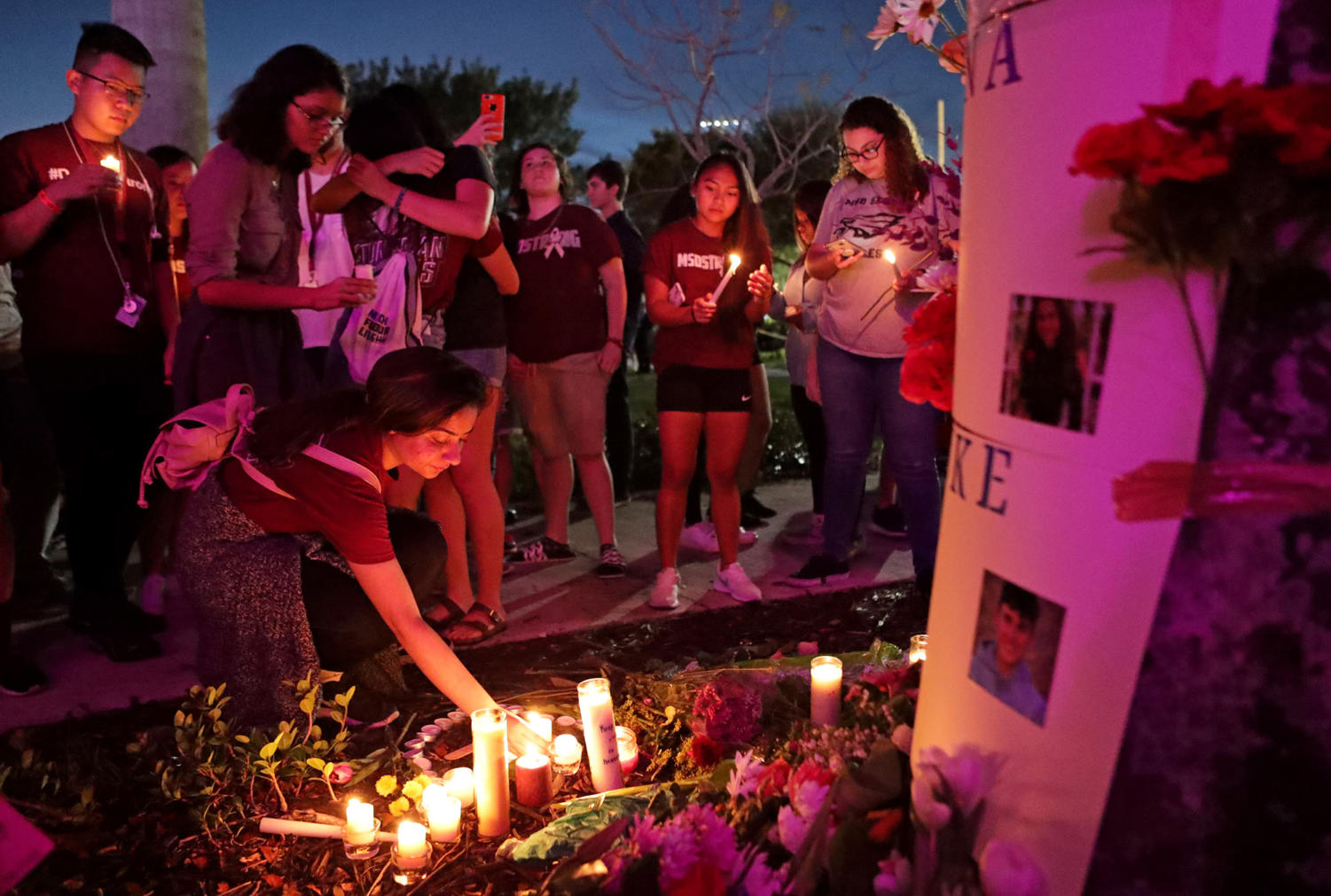 People light candles for a makeshift memorial after an interfaith ceremony at Pine Trails Park in Parkland, Fla., to remember the 17 victims killed last year at Marjory Stoneman Douglas High School, on Thursday, Feb. 14, 2019.