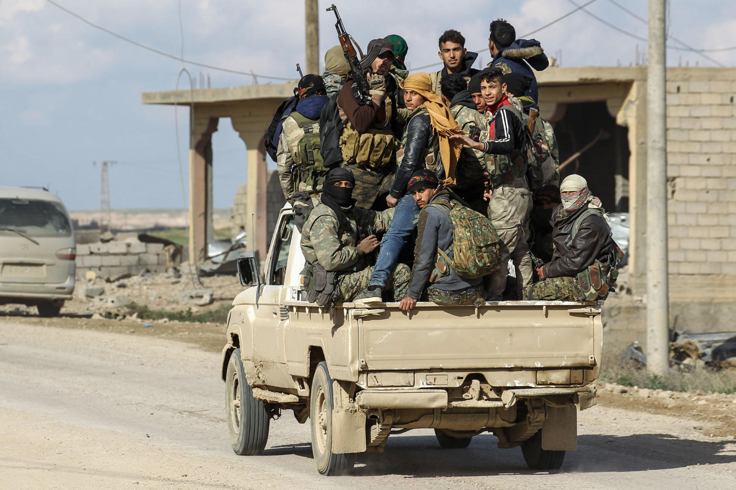 Fighters of the Syrian Democratic Forces, a U.S.-allied Kurdish-led rebel group, patrol through the Islamic State-held village of Baghouz in the eastern Syrian province of Deir Ezzor. SDF officials have said the extremists are clinging to an area less than a square kilometer in the village of Baghouz and preventing more than 1,000 civilians from leaving the area.