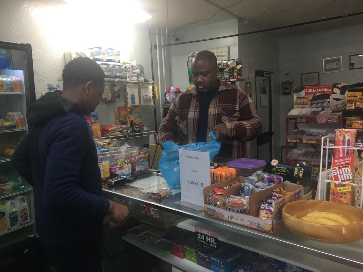 Carl Lewis bags a customer's purchase at his corner store.
