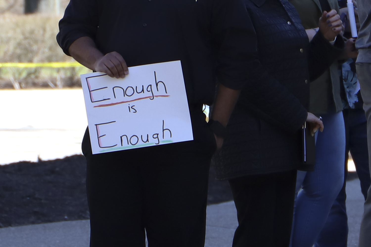 """A demonstrator holds a sign reading """"enough is enough"""" at the die-in demonstration organized by Black Action Society on Wednesday."""