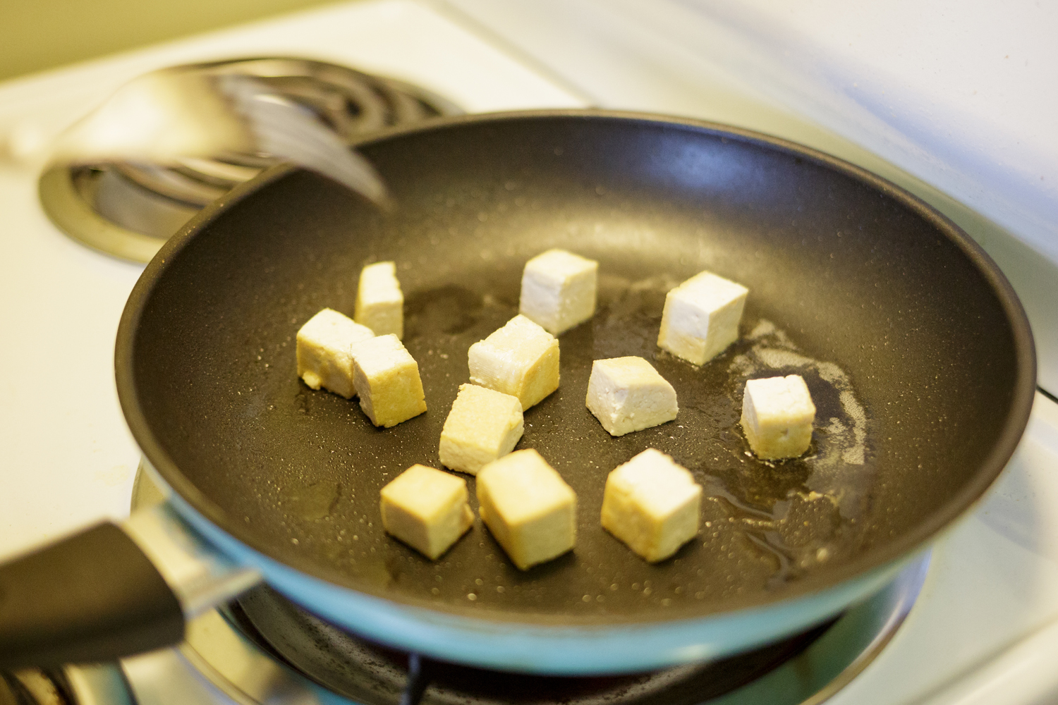 Tofu cooking in a pan.