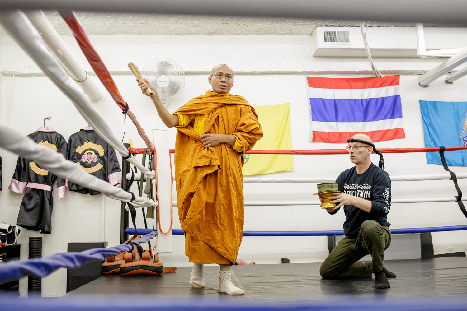 Sitkiatnin Muay Thai head instructor David Reese (right) assists with the blessing of the gym's ring by Thai Buddhist monks on Sunday morning. Sitkiatnin Muay Thai is a Thai boxing gym in the basement of 1918 Murray Avenue in Squirrel Hill.