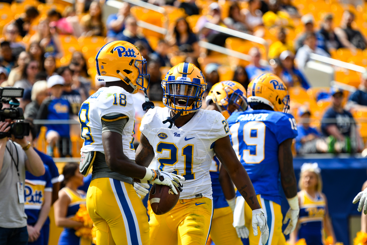 Junior running back A. J. Davis (21) and sophomore wide receiver Shocky Jacques-Louis (18) celebrate during Pitt's spring Blue-Gold game on Saturday.