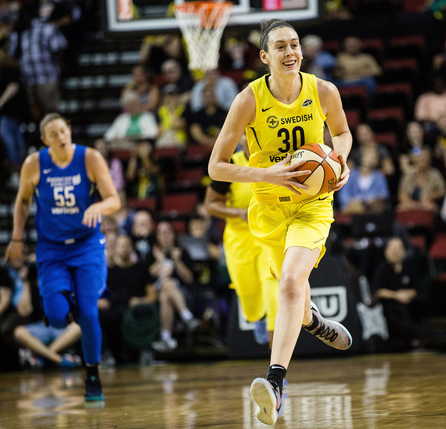 The Seattle Storm's Breanna Stewart smiles as she dribbles down the court after blocking a Dallas Wings shot on Aug. 19, 2018, at Key Arena in Seattle.