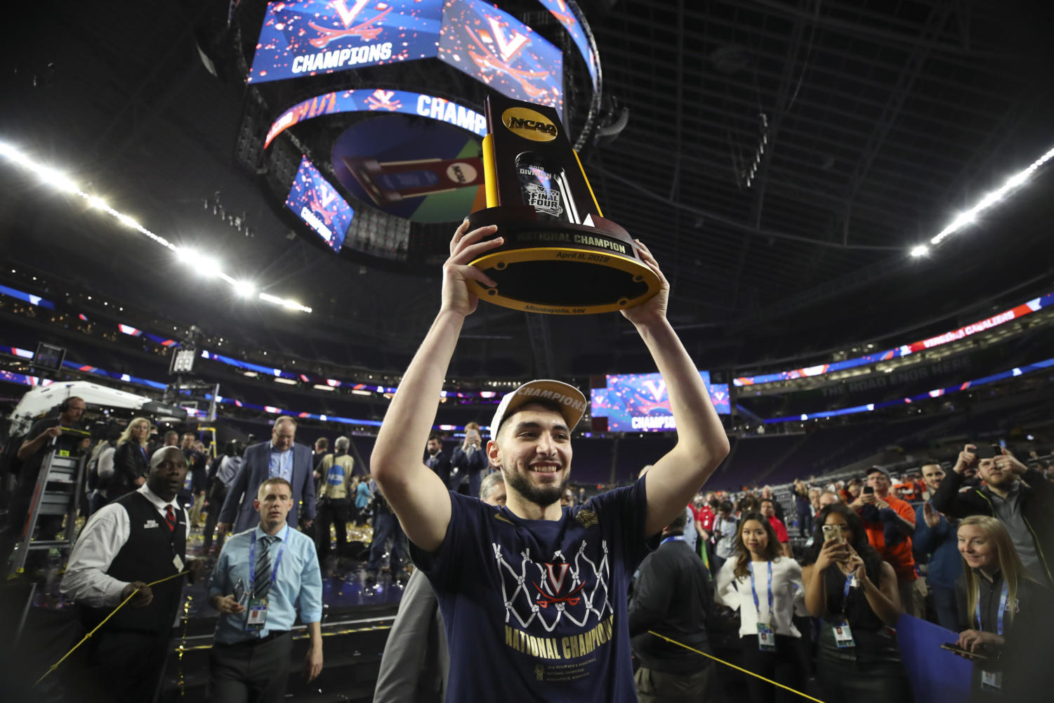 Virginia Cavaliers guard Ty Jerome hoists the championship trophy aloft as he walks off the court on Monday at U.S. Bank Stadium in Minneapolis. Virginia defeated Texas Tech 85-77 in overtime to win the NCAA Division I Men's Basketball Championship.