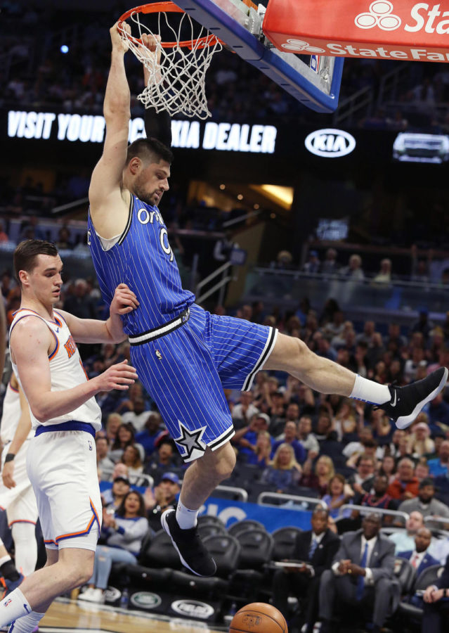 The Orlando Magic's Nikola Vucevic (9) dunks over the New York Knicks' Mario Hezonja, left, at the Amway Center in Orlando, Florida, on Wednesday, April 3. The Magic won, 114-100.