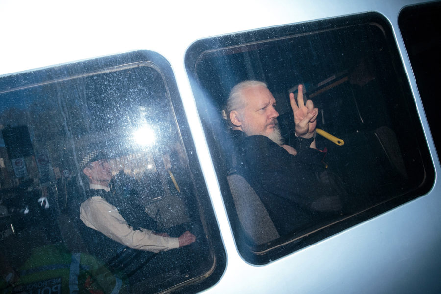 Julian Assange gestures to the media from a police vehicle on his arrival at Westminster Magistrates court on April 11 in London.