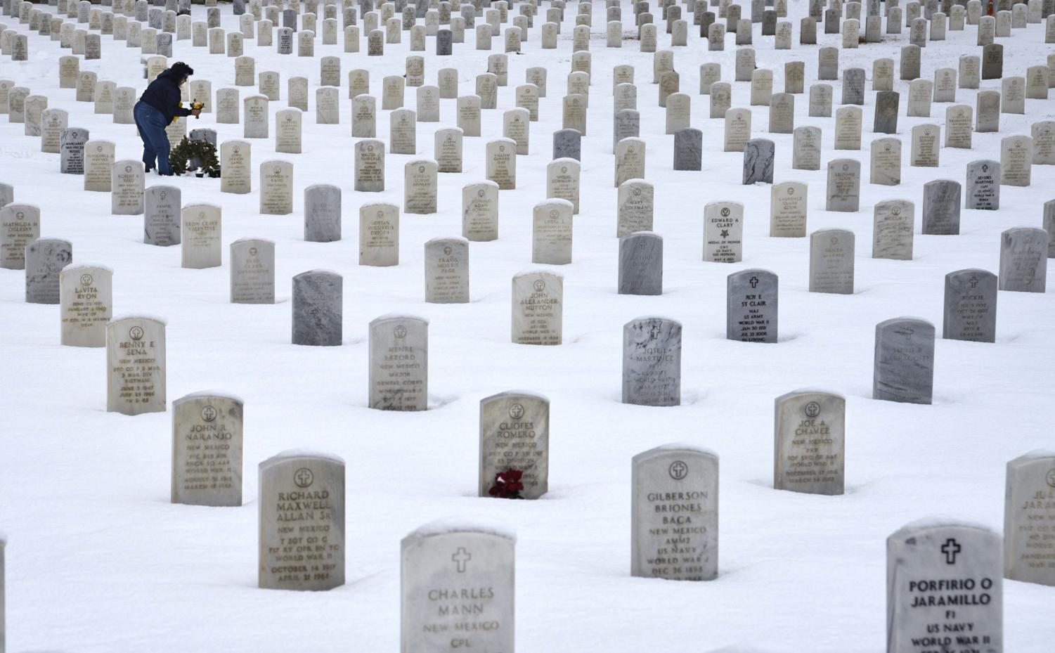 SANTA FE, NEW MEXICO - JANUARY 11, 2019: A woman places flowers on the grave of a loved one at the Santa Fe National Cemetery in Santa Fe, New Mexico, which is administered by the United States Department of Veterans Affairs. (Photo by Robert Alexander/Getty Images)