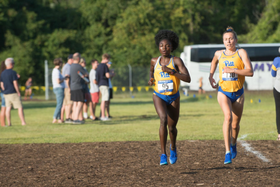 Pitt runners Brenda Ayuk, left, and Sam Shields, right, extend their lead on the second lap of the race. They would finish 2nd and 5th respectively and contribute to a Pitt team victory.