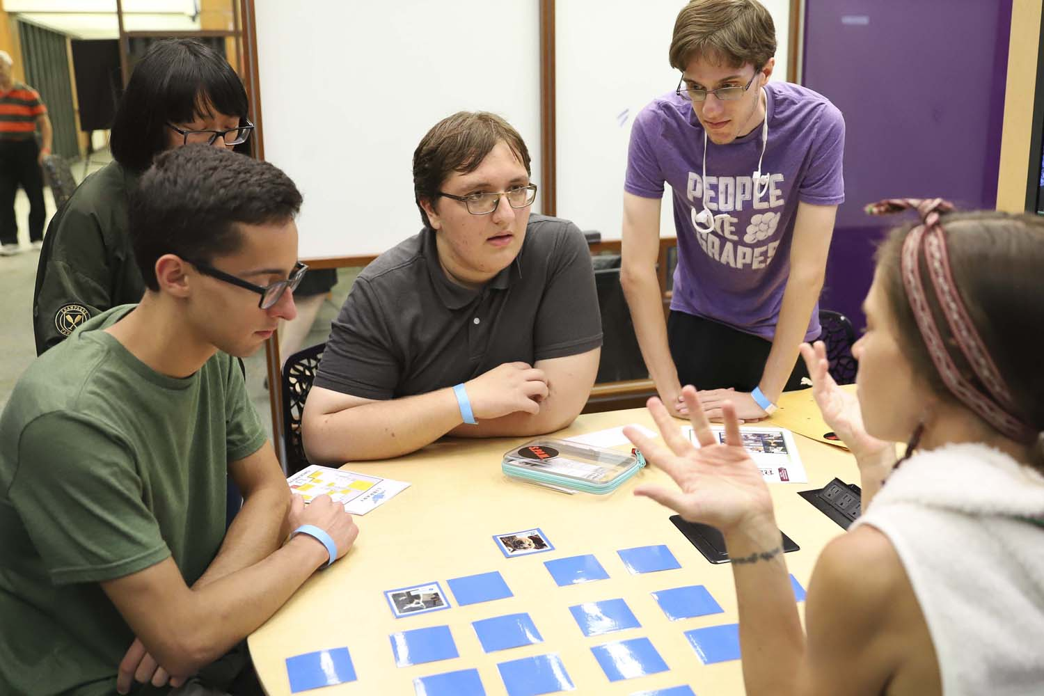 """Student's complete language-based puzzles at the Office of Less Commonly Taught Languages' """"Talk Your Way Out: Escape the Airport!"""" event in Hillman on Wednesday evening."""