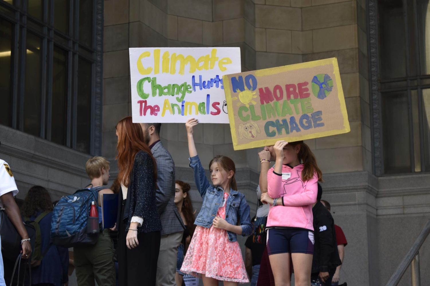 Students hold handmade signs in Downtown Pittsburgh at Friday's Youth Climate Strike.