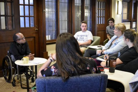 Chaz Kellem (far left), director of Pitt Serves, speaks with students at Thursday afternoon's Community Cafe event in the Cathedral of Learning.