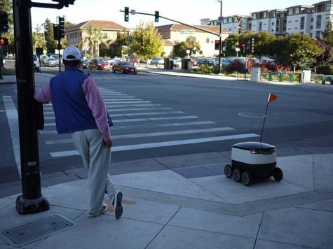 Man and Starship delivery robot waiting at pedestrian crossing in Redwood City, California.